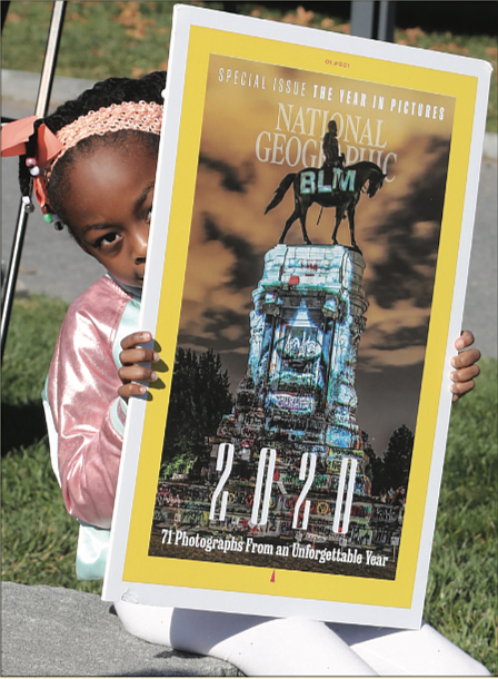 Storie Nzassi, the 7-year-old granddaughter of Delegate Delores L. McQuinn of Richmond, holds an enlarged copy of the cover of National Geographic Magazine's January edition featuring a projection of George Floyd's face on the statue of Confederate Gen. Robert E. Lee in Richmond. The Monument Avenue statue became a rallying point for protesters against police brutality and racial injustice following Mr. Floyd's death in May at the hands of a Minneapolis police officer. Images representing the struggle for civil rights and equality in the United States were projected onto the monument by Richmond artists Dustin Klein and Alex Criqui and photographed by Kris Graves for the cover. The youngster was attending a news conference last Friday with her grandmother at the Virginia Museum of Fine Arts, where Gov. Ralph S. Northam proposed $11 million in state funds be used to transform Monument Avenue.