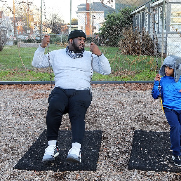 Clarence Thornton and his 5-year-old son, Chauncey, spend quality time together Tuesday at Hotchkiss Field in North Side. The youngster, a kindergartener at Richmond Prep, is close to his father and loves spending time outdoors with him. When the two are together, Mr. Thornton says he offers his son lessons on manners and how to play with other youngsters. The proud dad said young Chauncey received straight As on his first report card.