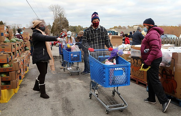 Volunteer Jeff Dean, 53, of North Chesterfield, center, maneuvers among the pallets of fresh fruit and produce where other volunteers fill his grocery cart with food. He then will load the food into one of the hundreds of cars waiting at the Chesterfield Food bank.