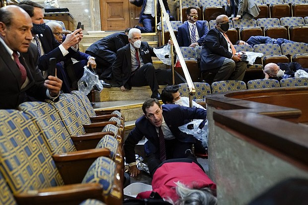 Members of Congress in the House gallery duck for shelter as protesters try to break into the House Chamber at the U.S. Capitol on Wednesday, Jan. 6  in Washington, D.C.    (AP photo)