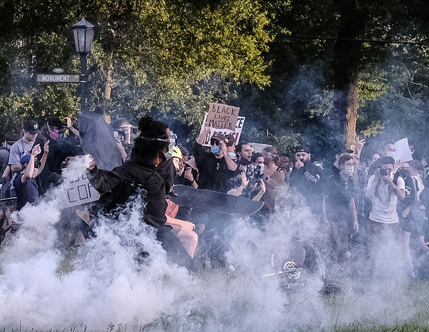Protesters participating in a peaceful demonstration react to being hit by Richmond Police with tear gas and pepper spray on Monument Avenue at the Robert E. Lee statue about 30 minutes before the city's 8 p.m. curfew on June 1.