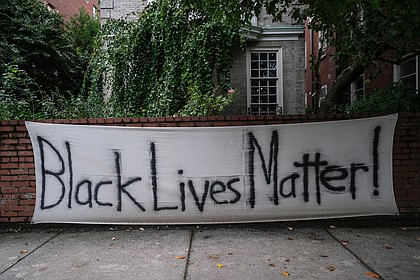 """A """"Black Lives Matter"""" banner hangs in October on the wall in front of a Monument Avenue residence near Allen Avenue, the epicenter of protests over racial injustice and police brutality since May. Signs like this one and logos with BLM have become commonplace on businesses and other buildings in and near Downtown and the Lee monument following an early spate of damage. The signs often were posted as a signal to spare the place from any damage."""
