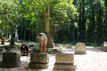 """Dr. Johnny Mickens III, right, the great-grandson of Maggie L. Walker, and his daughter, Liza Mickens, survey the damage discovered Aug. 3 at Mrs. Walker's gravesite in historic Evergreen Cemetery. Her headstone, entrances to the gravesite and the entrance to Sir Moses Montefiore Cemetery, a historic Jewish cemetery, were spraypainted with """"777,"""" numbers that are linked to white supremacist groups."""