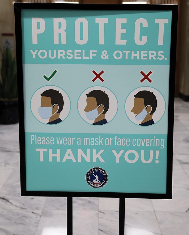 City Hall is being proactive in pushing safe practices during the pandemic. This sign was prominently displayed outside the second floor City Council Chambers on Monday before the nine council members were sworn in — including seven women, the most ever. Only a few people, mostly media and some family members, were allowed in the chamber for the ceremony. Others were able to connect to online channels to see the public ceremony.