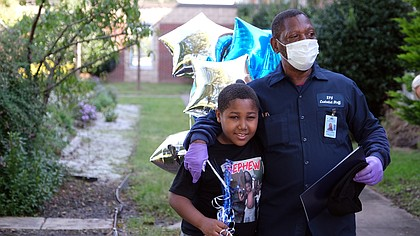 James Green, left, the custodian crew leader at Chimborazo Elementary School, receives a hug from his grandson, Mykhi Davis, 9, after being surprised Oct. 2 by Richmond Public Schools officials honoring him for 43 years of service to RPS students and families. The occasion was National Custodial Workers Day.