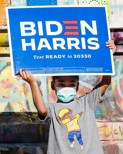 Aiden Porter holds up a Biden-Harris campaign sign Nov. 7 in celebration of the Democrats' victory in the presidential election. The 4-year-old stood at the base of the Lee statue on Monument Avenue, where he was celebrating with his mother, Jasmine Howell.