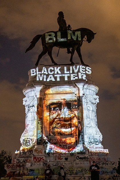A Black Lives Matter tribute to the late George Floyd is projected onto the statue of Confederate Gen. Robert E. Lee on the evening of June 6 by local artist Dustin Klein, a striking signal of change. The statue and grounds on Monument Avenue became a central point for demonstrators and others seeking a metamorphosis in the city.