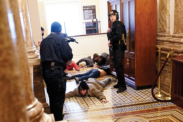 U.S. Capitol Police hold protesters at gunpoint near the House Chamber inside the Capitol. The Trump mob broke windows and forced their way into the building, which went on lockdown.