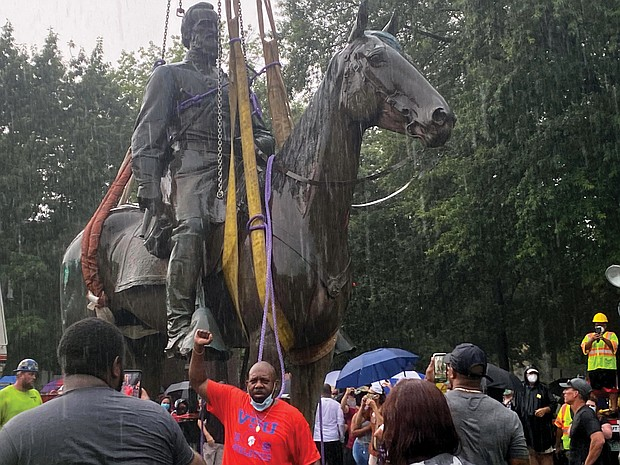 """A cheering crowd watches as a crane hauls away the massive, 100-year-old statue of Confederate Gen. Thomas """"Stonewall"""" Jackson from its pedestal at Monument Avenue and Arthur Ashe Boulevard during a downpour on July 1. Using an emergency declaration, Mayor Stoney ordered the city-owned Confederate statues to be removed as a public safety measure."""