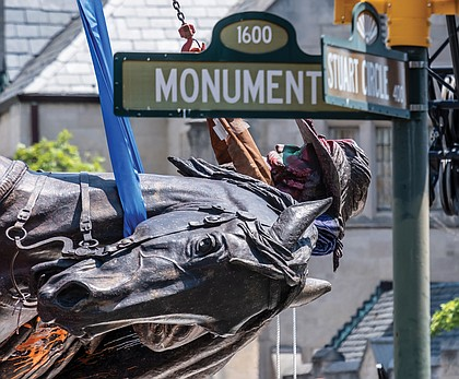 The statue of Confederate Gen. J.E.B. Stuart is turned on its side and lowered onto a flatbed truck on July 7 after being taken from its pedestal at Monument Avenue and Stuart Circle. It was sent to storage as the city worked out a plan for disposal.