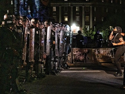 A protester confronts Virginia State Police troopers, who declared an unlawful assembly before pepper-spraying peaceful protesters and bystanders on June 26.