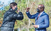 Jon Ossoff, left, and Raphael Warnock exchange elbow bumps Monday during a campaign rally in Augusta, Ga. Democrats Ossoff and Warnock won their respective racdes against incumbent Republican Sens. David Perdue and Kelly Loeffler in a runoff election Jan. 5.