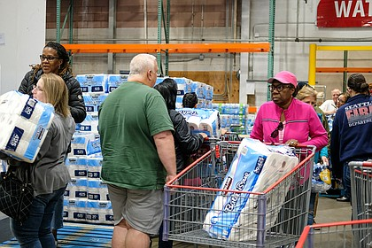 Customers flock to the pallets of toilet paper at Costco on March 14 as the initial threat of coronavirus and a statewide shutdown causes consumers to make a run on paper products, cleaning supplies and food staples at area stores.