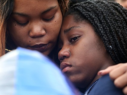 Shaniqua Allen embraces her 14-year-old daughter, Ni'Aveya Allen, during a prayer vigil Feb. 8 for Mrs. Allen's 3-year-old son, Sharmar L. Hill Jr., who was shot and killed by gunfire while playing outside the family's home in the Hillside Court public housing community on Feb. 1.