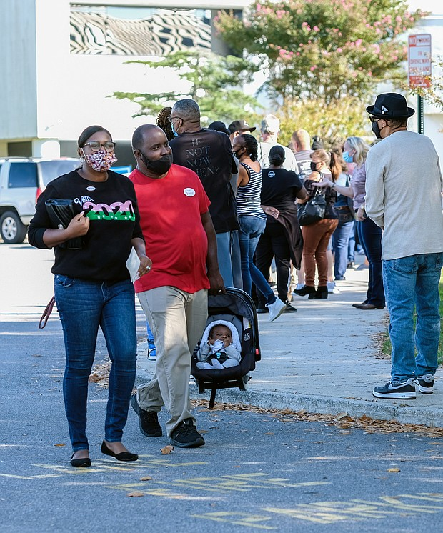 Kindal and George White give their 4-month-old son, Greyson, his first taste of voting as hundreds turned out at the Eastern Henrico Government Center on Nine Mile Road for early, in-person voting on Oct. 24. Lines were common at many early- voting sites throughout Metro Richmond.