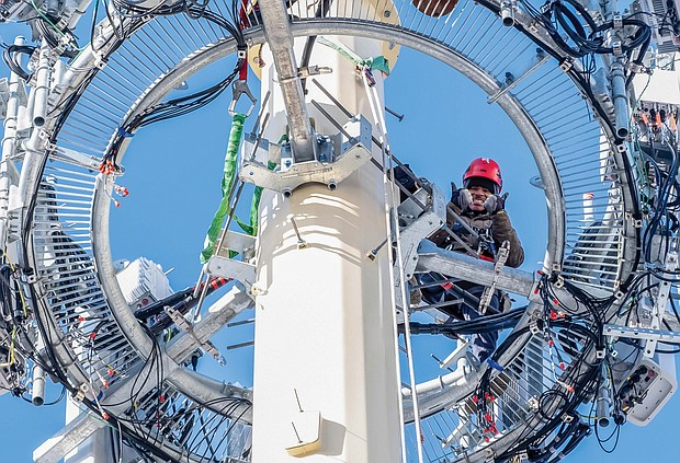 A Verizon worker doing maintenance work atop a cell tower pauses for a photo op. Location: 25th and Decatur streets in South Side.