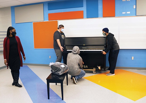 The piano was placed in the music room of the new school, where students will be able to enjoy it once in-person learning resumes.