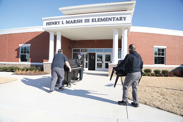 A crew from Famous Jerry Piano Moving in Disputanta moves a new Yamaha piano into Henry L. Marsh III Elementary School on Tuesday under the watchful and excited guidance of Principal Kimberly Cook.