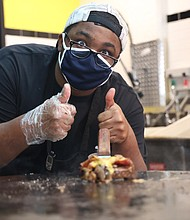 Grill Master— Employee Michael Jones cooking a Noisy Burger on the grill.