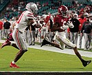 Alabama wide receiver and Heisman Trophy winner DeVonta Smith, right, runs past Ohio State University safety Josh Proctor to score a touchdown during the first half of the NCAA College Football Playoff National Championship on Monday night in Miami.