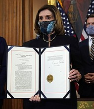 House Speaker Nancy Pelosi displays the signed article of impeachment against President Donald Trump charging him with incitement of insurrection over the deadly siege on the U.S. Capitol on Jan. 5. The document was displayed Wednesday, Jan. 13 during an engrossment ceremony before its transmission to the Senate for trial.  (AP photo)