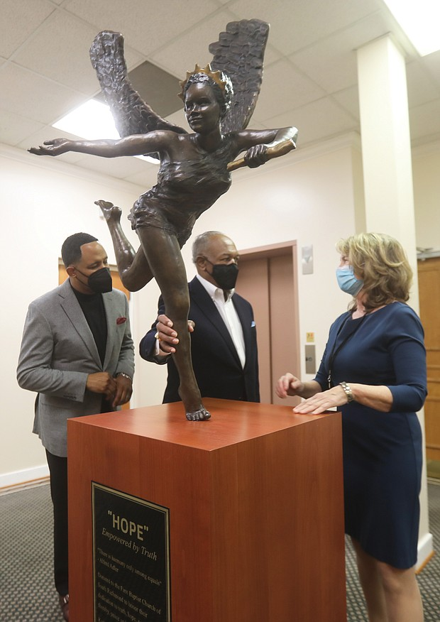 """Dr. Derik E. Jones, left, and Dr. Dwight C. Jones, pastors of First Baptist Church of South Richmond, get a closer look at the new bronze sculpture """"Hope Empowered by the Truth"""" with its creator, local artist Kathleen Lowry. The 150-pound sculpture was unveiled at the Decatur Street church on Monday, the Martin Luther King Jr. Holiday, during a ceremony viewed online by more than 200 people. Ms. Lowry donated the piece to the church after attending the socially distanced kickoff last September of First Baptist's yearlong 200th anniversary celebration. She said the church seemed like the perfect home for the sculpture. """"It is recognition of the work you do every day to promote peace in our country,"""" she said during Monday's event. """"Martin Luther King knew what would be necessary — faith, hopefulness, truth-telling, courage, resilience, kindness and forgiveness. And that is what you are doing and being in the struggle for equality and peace. It is an extremely tall order."""" Members of the congregation will be able to see the artwork once the church reopens for in-person worship service. The church has held virtual services because of the pandemic."""