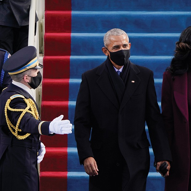 Former President Barack Obama and his wife, former First Lady Michelle Obama, arrive to applause at the U.S. Capitol for the historic swearing in ceremony of Vice President Kamala Harris and President Joe Biden. The nation's first African-American president took the oath of office from the same spot at the West Front of the Capitol on Jan. 20, 2009, and again on Jan. 21, 2013.
