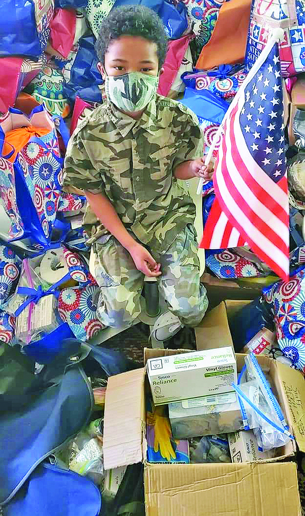 """Tyler, 9, has given away thousands of his """"Hero Bags"""" and """"Hero Boxes"""" with toiletries, clothing and other items to thank veterans."""