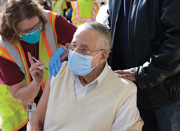 McKinley Woodson, 93, gets vaccinated by Kathleen Sardegna at the mass vaccination effort Saturday at Richmond Raceway. Son Kelvin Woodson helped his dad and his 80-year-old mother, Bernice Woodson, navigate the process.