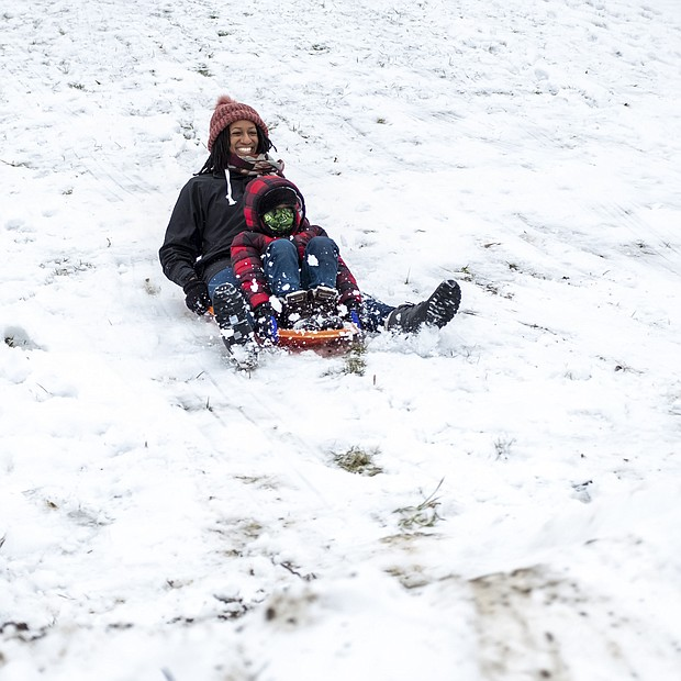 Tamra Collins and her 6-year-old son, Isaiah, happily sled down a hill at Shrader Road and Eunice Drive last Sunday in Henrico County. When 3 inches of snow hit the metro area last weekend, people took to the outdoors to enjoy the wintry landscape. People were sledding, had snowball fights and built snowmen. While this was Metro Richmond's first big snowfall of the winter season, the area escaped the 1 to 3 feet of snow the same storm dropped on the Northeast. Much of the snow has melted already, with more wet weather on the way. Rain is expected Friday, Feb. 5, with the possibility of rain and/or snow showers on Sunday, Feb. 7. Nightly temperatures are forecast to remain at or below freezing through next week.