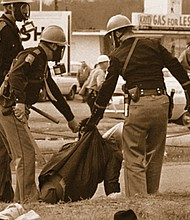 """An Alabama state trooper grabs a woman as police break up the 1965 Selma to Montgomery civil rights march pressing for voter registration rights for Black Americans across the South. The violent response by police became known as """"Bloody Sunday.""""  (AP photo)"""