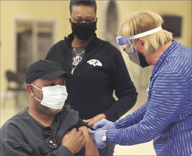 Sylvia Jones, 68, watches as her husband, George Jones, 69, receives his first shot of the COVID-19 vaccine. The couple, members of Second Baptist Church of South Richmond, were inoculated during a vaccine event held at the church by the Richmond and Henrico health districts.