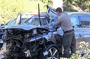 A law enforcement officer looks over the damaged vehicle involving golfer Tiger Woods, following a rollover accident Tuesdayin the Rancho Palos Verdes suburb of Los Angeles. Woods suffered serious leg injuries in the one-car accident.  (AP photo)