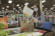 Sara Plush, a Portland Fred Meyer store employee, adds a sheet with information about how to get a COVID-19 vaccine. An untold number of older people are getting left behind in the desperate dash for shots because they are too frail, overwhelmed, isolated or poor to navigate a system that favors healthier individuals with more resources. (AP photo)