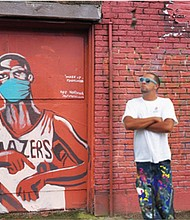 "Wearing a mask and pointing to his watch in a ""Dame Time"" pose, Portland's Damian Lillard is depicted in a new Portland mural to remind people to wear masks in solidarity against COVID-19.  The artwork at Northeast 28th and Alberta was created by Portland artist and muralist Kyle Holbrook who poses in front of his creation."