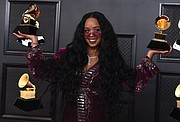 """H.E.R. poses in the press room with the award for song of the year for """"I Can't Breathe"""" and best R&B song."""