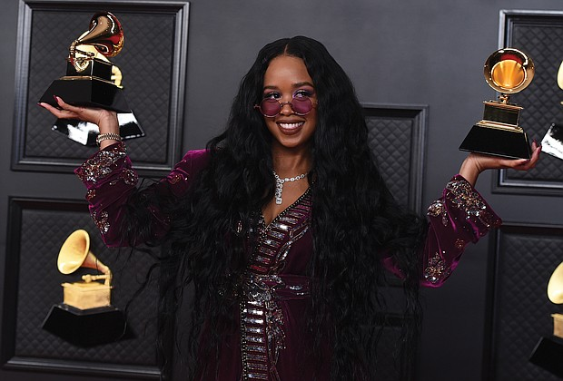 "H.E.R. poses in the press room with the award for song of the year for ""I Can't Breathe"" and best R&B song."