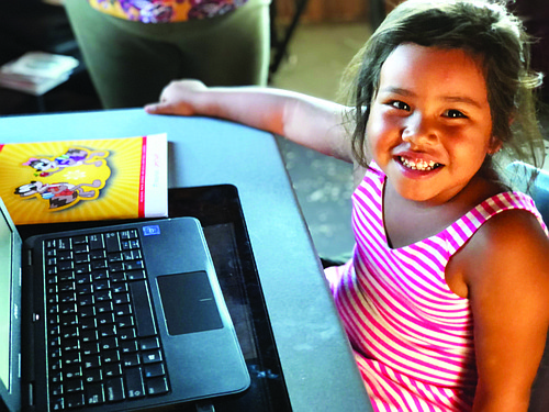 Kylie Yellowman Williams from the Navajo Nation flashes a big grin as she opens her new computer for the first time.
