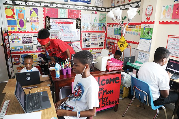 Tisha Erby keeps things moving and the learning going for her four school-age sons in their family's home. The living room has been turned into a vibrant classroom, with desks and laptops for each of the boys. They are, from left, Emanuel, 3, a pre-schooler at Summer Hill Elementary; Christopher Jr., 13, a seventh-grader at River City Middle School; Elijah, 5, a kindergartner at J.L. Francis Elementary; and Lamar, 11, a sixth- grader at River City Middle. Seated in a high chair in the room, but not pictured, is year- old Tristan, who was working on his own activities given to him by his mom.