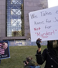 Demonstrators in Minneapolis hold signs outside the justice center where the trial for former Minneapolis police officer Derek Chauvin began on Monday, March 29 with opening statements from both sides. Chauvin is charged with murder in the death of George Floyd during an arrest last May in Minneapolis. (AP photo)