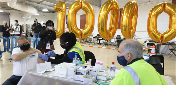 """Tom Leonard, 65, owner of Tom Leonard's Farmer's Market in Short Pump, holds up his sleeve as nurse Antwon Agee administers his second shot of the Pfizer vaccine last Saturday. Mr. Leonard received the 100,000th dose of the vaccine given at clinics at the Richmond Raceway. """"I feel pretty special today,"""" he said."""