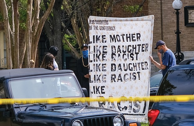 Anti-racist demonstrators hold a banner Saturday outside the headquarters of the United Daughters of the Confederacy on Richmond's Arthur Ashe Boulevard. The two said they are not affiliated with the White Lies Matter group that claimed responsibility for stealing a Confederate chair from a Selma, Ala., cemetery in March and then demanding the UDC post a banner at the Richmond headquarters on April 9, the anniversary of the Confederate surrender at Appomattox, ending the Civil War. The two demonstrators had their own message for the UDC.