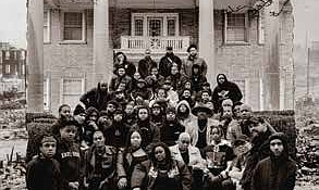 Fire in Little Africa artists pictured in front of the Skyline Mansion, a now Black-owned venue originally built by a KKK leader who helped orchestrate the 1921 Tulsa Race Massacre. This photo is inspired by a group photo of original Black Wall Street business owners from before 1921. Photo Credit: Ryan Cass