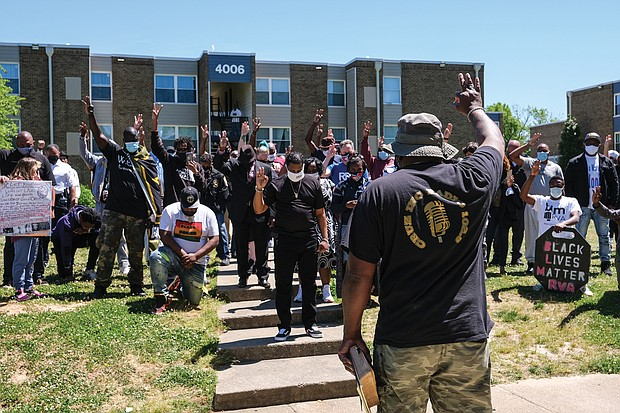 """Cruz Sherman, founder of Men in Action, leads a prayer during a rally Saturday of community members and public officials seeking solutions to stop the city's gun violence. Group members hold up three fingers in tribute to 3-month-old Neziah Hill, who was shot and killed with her 30-year-old mother, Sharnez Hill, on April 27 in the courtyard of the Belt Atlantic Apartments on Midlothian Turnpike. Three others were wounded. The rally was held in view of the apartment complex. Among the officials attending the rally were U.S. Sen. Tim Kaine, state Sen. Joseph D. """"Joe"""" Morrissey, Richmond Police Chief Gerald M. Smith, Henrico Police Chief Eric D. English, Richmond Sheriff Antionette V. Irving, Richmond Commonwealth's Attorney Colette W. McEachin, Richmond Public Schools Superintendent Jason Kamras and Henrico County Sheriff Alisa Gregory."""