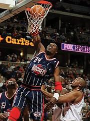 In this Jan. 28, 2000, file photo, Houston Rockets center Hakeem Olajuwon dunks the ball over Denver Nuggets center Popeye Jones during a game in Denver.