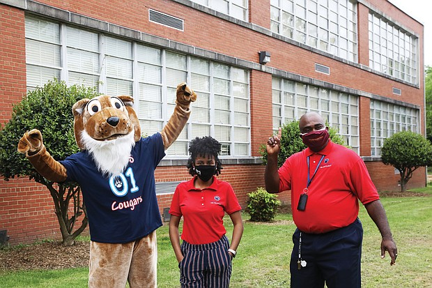 Ashley Bland pauses for a photo with John B. Cary's Principal Michael Powell and the school mascot following the announcement.