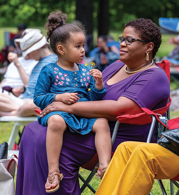 Mommy and me time/Emmie Aslan, 3, sits with her mother, Joli Aslan, while they enjoy the music of the Desiree Roots Jazz Trio at last Saturday's outdoor concert at The Cultural Arts Center at Glen Allen.