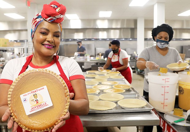 Joye B. Moore shows off one of her Joyebells Sweet Potato Pies at her production facility at Hatch Kitchen RVA in South Side. Working behind her are her sister, left, Cassandra Wheeler, director of production, and Kanesha Johnson, lead production team member.