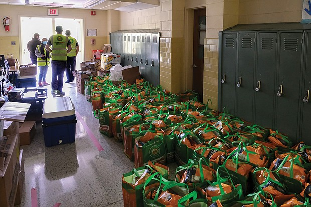 Tote bags filled with food and staples line the hall of Quioccasin Middle School, where volunteers with ICNA Relief and Henrico County Public Schools helped distribute them Saturday to more than 100 families in need who picked up the bags curbside.