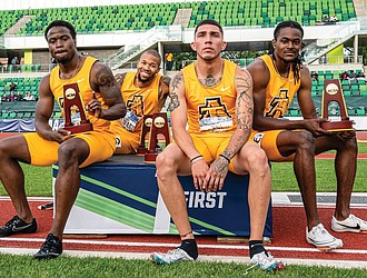 North Carolina A&T State University sprinters, from left, Akeem Sirleaf, Trevor Stewart, Daniel Stokes and Randolph Ross Jr. show off their trophies from winning the 4x400 meter relay last weekend at the NCAA Outdoor Track and Field Championships in Oregon.